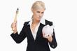 Serious businesswoman holding a hammer and a piggy-bank