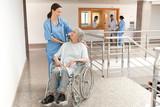 Nurse watching over old women sitting in wheelchair