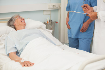 Elderly female patient smiling up at nurse and doctor