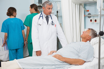 Patient  lying in bed talking to  doctor