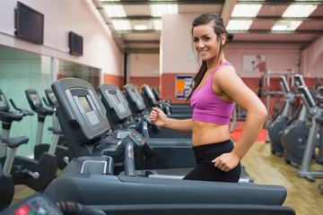 Woman running on a treadmill in a gym looking happy