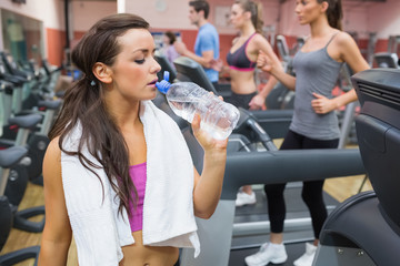 Woman drinking water beside treadmill