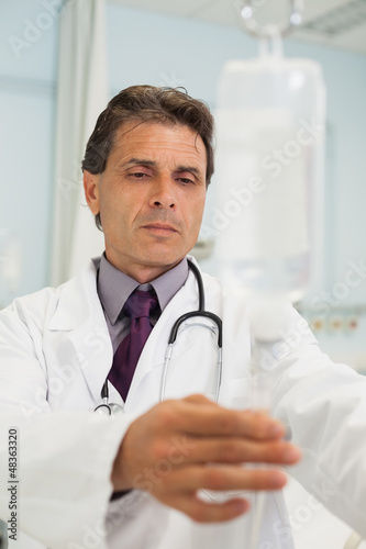 Thoughtful doctor in a hospital adjusting IV