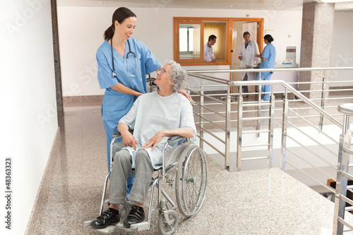 Nurse watching over old women sitting in wheelchair