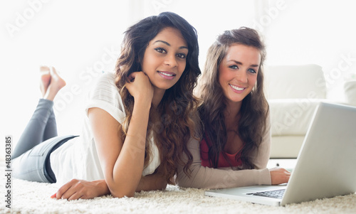 Two smiling women typing on a computer while lying on the floor