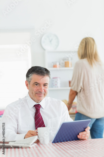 Smiling man with tablet pc and coffee at kitchen table