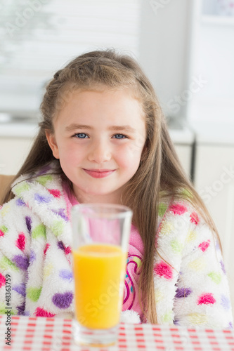 Little girl sitting while smiling with glass of orange juice