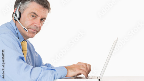 Man writing on his laptop with headset