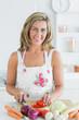 Smiling woman preparing vegetables