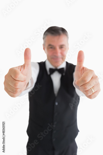 Smiling waiter having thumbs up