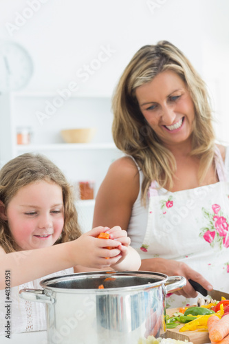 Laughing mother and daughter preparing vegetables