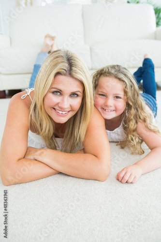 Mother and daughter resting on the carpet