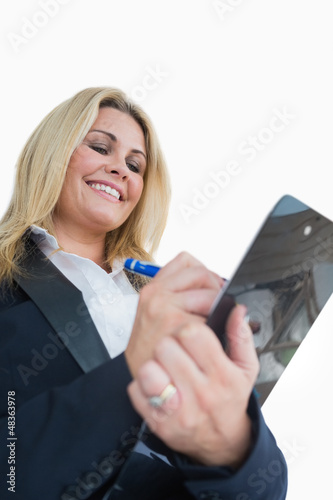 Happy business woman writing in the clipboard