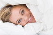 Smiling woman hiding under the duvet