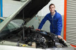 Repairman standing by car with open hood