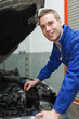 Auto mechanic checking car engine oil