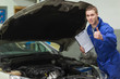 Mechanic with clipboard gesturing thumbs up