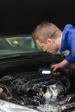 Repairman examining car engine