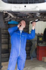 Mechanic on call as he examines car