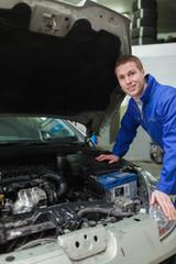 Happy mechanic repairing  car engine