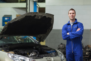 Confident mechanic standing by car