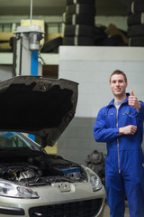 Mechanic by car gesturing thumbs up