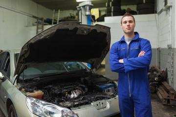 Confident auto mechanic by car