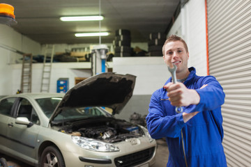 Mechanic offering spanner in worshop