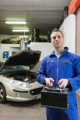 Confident auto mechanic with car battery