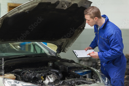 Mechanic with clipboard examining car engine