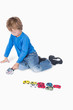 Young boy playing with playhouse and toy cars