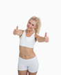 Happy woman in sportswear giving thumbs up