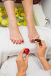 Woman applying nail varnish to toe nails at spa center