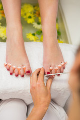 Woman polishing toe nails at spa center