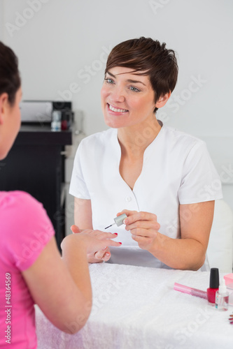 Nail technician applying nail varnish to finger nails