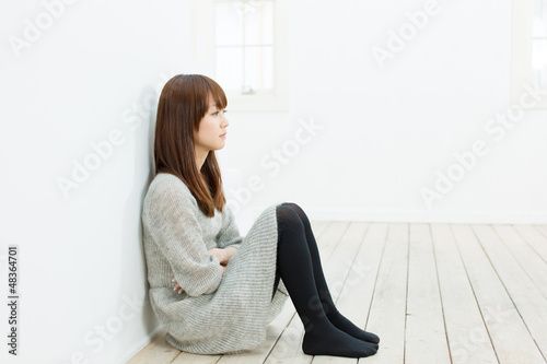 Beautiful sad woman sittiing in the room