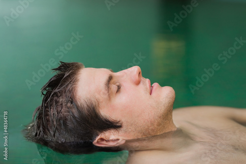 Handsome man floating in the pool