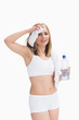 Sporty woman holding water bottle and wiping sweat with a towel