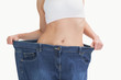 Midsection of female wearing old pants after losing weight
