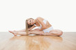Portrait of young  woman stretching on hardwood floor