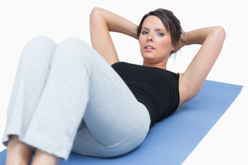 Portrait of woman doing sit-ups on exercise mat over