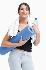 Portrait of woman in sportswear holding water bottle and mat