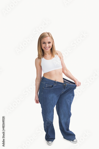 Portrait of woman wearing old pants after losing weight