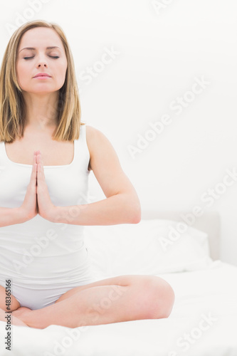 Woman in praying position with eyes closed on bed