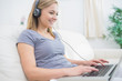 Woman listening music through headphones while using laptop