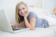 Young woman lying on couch and using laptop