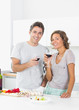 Couple drinking red wine and preparing salad