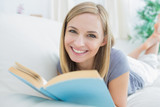 Portrait of happy woman with storybook lying on couch