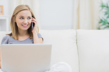 Casual woman using laptop and cellphone at home