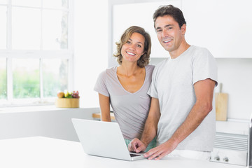 Couple standing in kitchen with laptop